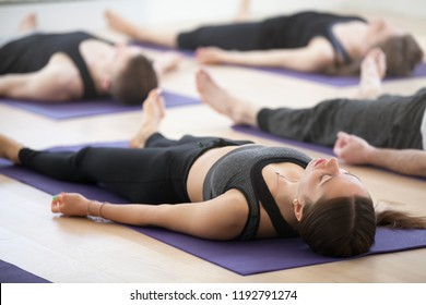 Group of young sporty people practicing yoga lesson, doing Dead Body, Savasana, exercise Corpse pose, working out, indoor, students training in club, studio close up. Well-being concept