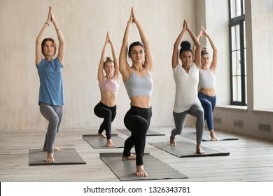 Group of young sporty people practicing yoga lesson, doing Warrior one pose, Virabhadrasana 1 exercise, working out, indoor close up, mixed race students training at sport club, white yoga studio