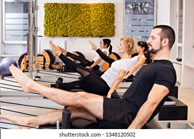 Group of young sporty people practicing fitness lesson with instructor, doing warming up exercise at tower reformer, boat pose, working out, students training in club, friends at fitness lesson