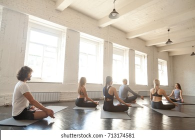 Group of young sporty people practicing yoga lesson with instructor, sitting in Sukhasana exercise, doing Easy Seat pose, working out, indoor full length, big light studio. Wellbeing, wellness concept