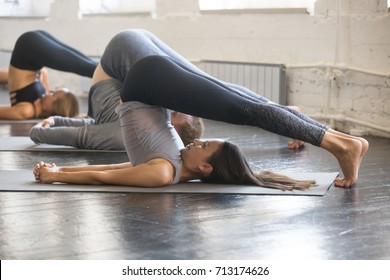 Group of young sporty people practicing yoga lesson with instructor, stretching in Halasana exercise, Plough pose, working out, indoor full length, studio. Wellbeing, wellness concept