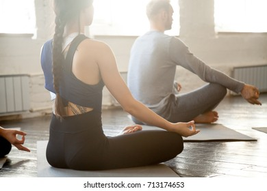 Group of young sporty people practicing yoga lesson with instructor, sitting in Sukhasana exercise, doing Easy Seat pose, working out, indoor close up, studio. Wellbeing and wellness concept
