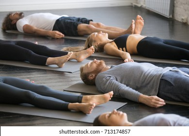 Group of young sporty people practicing yoga lesson with instructor in gym, lying in Dead Body exercise, doing Savasana, Corpse pose, friends relaxing after working out in sport club, indoor image