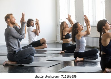 Group of young sporty people practicing yoga lesson with instructor, sitting in Gomukasana exercise, Cow Face pose, friends working out in club, indoor full length, studio. Wellbeing, wellness concept