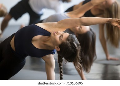 Group of young sporty people practicing yoga lesson with instructor, stretching in Bending Side Plank exercise, Vasisthasana pose, working out, indoor close up image, studio, smiling woman in focus