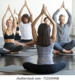 Group of young sporty people practicing yoga lesson with instructor, sitting in Sukhasana exercise, Easy Seat pose, friends working out in club, rear view at the teacher, indoor full length, studio