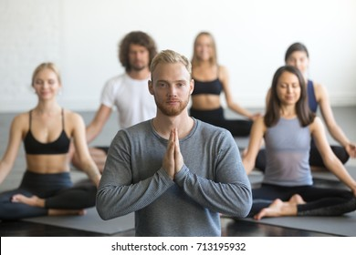 Group of young sporty people practicing yoga lesson with instructor, sitting in Sukhasana exercise, Easy Seat pose, friends working out in club, focus on male student, making mudra gesture, studio