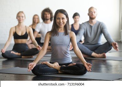 Group of young sporty people practicing yoga lesson with instructor, sitting in Sukhasana exercise, Easy Seat pose, friends working out in club, focus on woman in Padmasana, indoor full length, studio