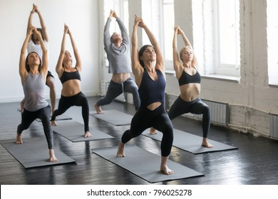 Group of young sporty people practicing yoga lesson with instructor, stretching in Warrior one exercise, Virabhadrasana 1 pose, working out, indoor full length, studio