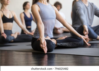 Group of young sporty people practicing yoga lesson with instructor, sitting in Padmasana exercise, Lotus pose, working out, indoor close up, focus on mudra gesture, students training in club, studio