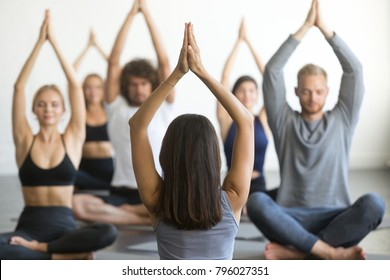 Group of young sporty people practicing yoga lesson with instructor, sitting in Sukhasana exercise, Easy Seat pose, working out, students training in club, indoor, studio. Wellness wellbeing concept