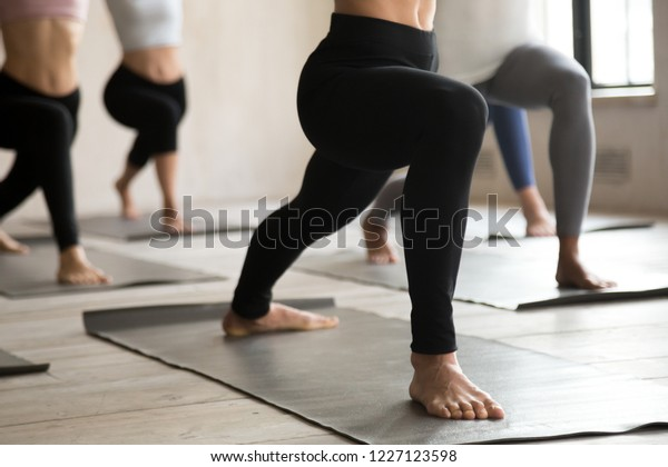 Group of young sporty people practicing yoga lesson, doing Warrior one pose, Virabhadrasana 1 exercise, working out, indoor close up, students training at club or yoga studio. Leg stretching concept