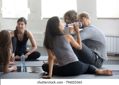 Group of young sporty people resting after working out. Students enjoying time together, sharing experiences of exercise program, refreshing with water