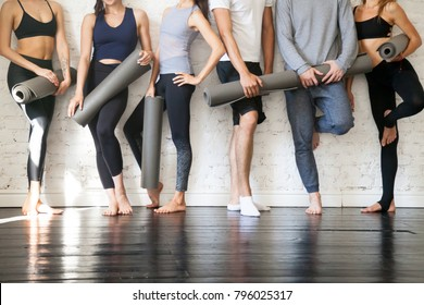 Group of young sporty people standing at wall. Students taking a rest from fitness activity, time to recover strength, waiting for a lesson to start in loft studio, close up. Healthy lifestyle concept