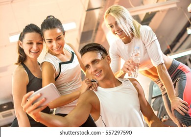 Group of young sporty people taking a selfie on smartphone after exercising in gym.