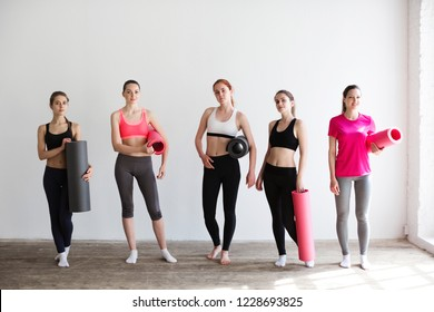 Group of young sporty woman with yoga mats standing at white wall. Female in gym after fitness.
