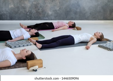 Group of young sporty women practicing yoga lesson, doing Dead Body, Savasana, exercise Corpse pose. Well being, health and relax concept