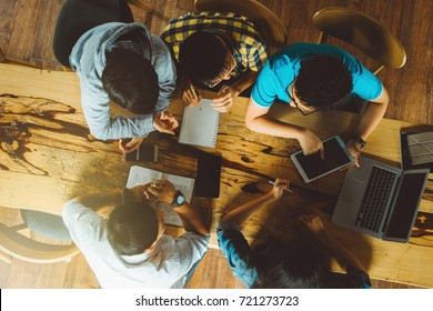 Group of young student sitting at a cafe, talking and enjoying, top view
