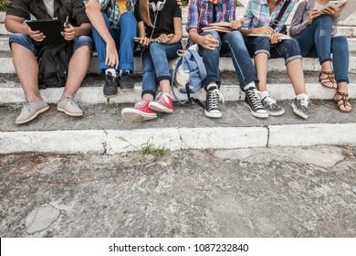 group of young students with books and gadgets sit on the steps in the park. unrecognizable