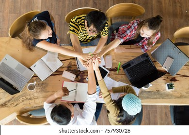 Group of young students in cooperation with their academic assignment. Top view shot of young people studying together around a table. students together at school table working homework and have fun.