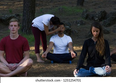 Group of young students following meditation class lead by female teacher in forest park. Woman guiding mindfulness exercise with hand on man's head. Inner self connection, inspiration moment concepts