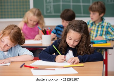 Group of young students in school with focus to a pretty young girl in the front row working on her class notes