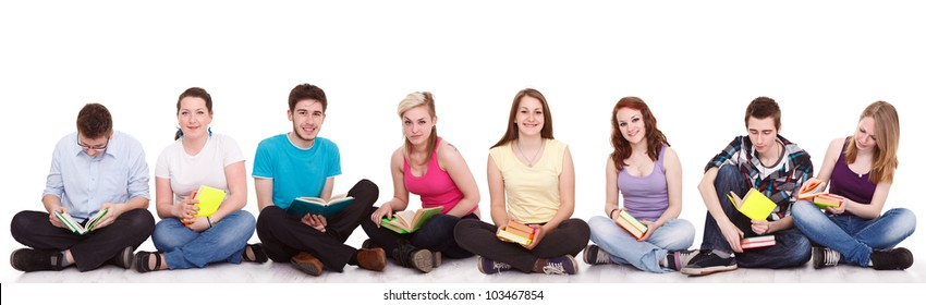 group of young students sitting on the floor  with books,  isolated on white background