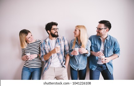 Group of young stylish happy people leaning against the wall and talking while drinks coffee in the paper cup.