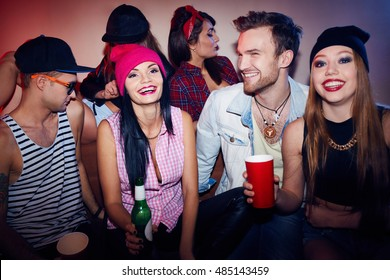 Group of young stylish men and women chilling out at awesome house party, laughing, drinking alcohol and enjoying time together