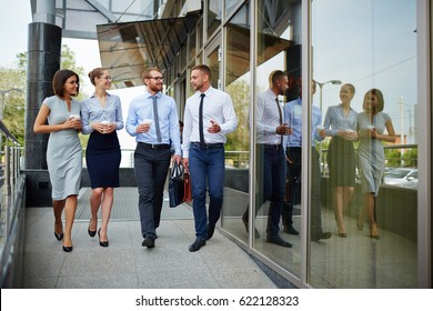 Group of young successful business people leaving modern office building and smiling cheerfully chatting on the way
