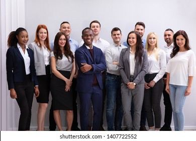 Group Of Young Successful Multi-ethnic Businesspeople Standing In Office Looking At Camera