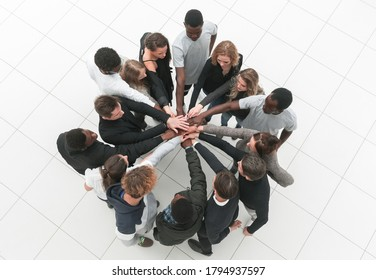 group of young successful people stands around hands together