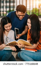 A group of young or teen Asian student in university smiling and reading the book and look at the tablet or laptop computer in summer holiday.