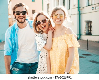 Group of young three stylish friends posing in the street. Fashion man and two cute girls dressed in casual summer clothes. Smiling models having fun in sunglasses.Cheerful women and guy at susnet