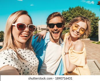 Group of young three stylish friends in the street.Man and two cute female dressed in casual summer clothes.Smiling models having fun in sunglasses.Women and guy making photo selfie on smartphone