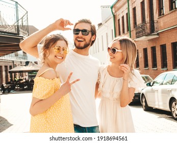 Group of young three stylish friends posing in the street. Fashion man and two cute female dressed in casual summer clothes. Smiling models having fun in sunglasses.Cheerful women and guy outdoors