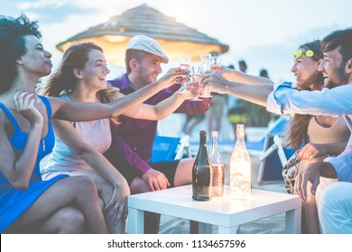 Group of young tourist friends cheering with champagne at beach kiosk party - Happy people having fun in summer holidays - Focus on hands glasses - Fun,vacation, summer lifestyle and youth concept