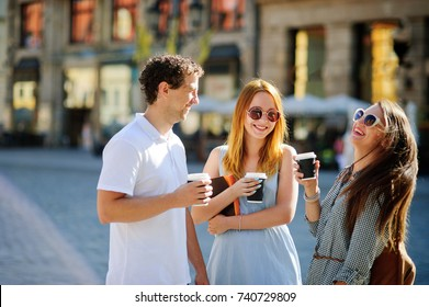 Group of young tourists stroll through the streets of an ancient city. Against the backdrop of beautiful buildings. In the hands of friends, paper cups with coffee. Warm summer day. Good mood.