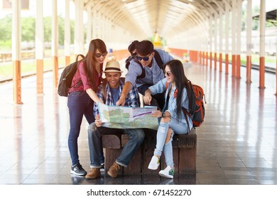 Group of young traveler looking map at train station.