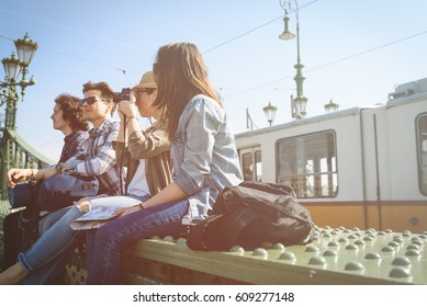 a group of young travelers, enjoying the beautiful sunny day during a break, sitting on a bridge