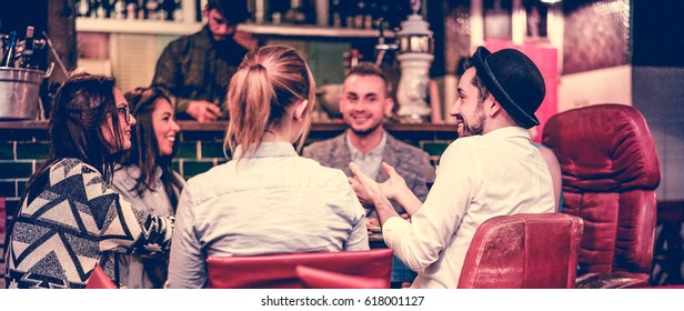 Group of young trendy friends chatting and laughing together inside cocktail fashion bar - Cheerful people having fun doing pre dinner appetizer - Focus on right man face - Vintage filter