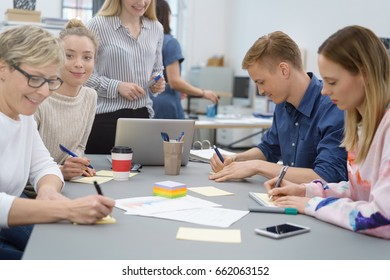 Group of young university students or business colleagues working together grouped around a table writing notes