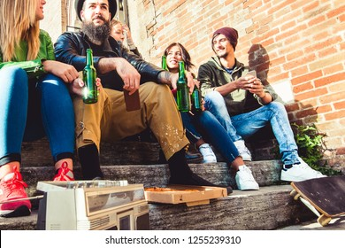 group of young urban friends enjoying  drinking bottles of beer outside in the town sharing a pizza. hipsters having fun concept.