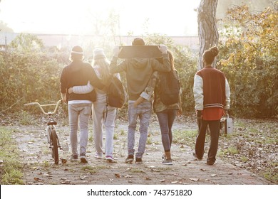 group of young urban friends walking in the park in autumn.  concept of college mates chilling together outdoors. light orange color sun flare filter.