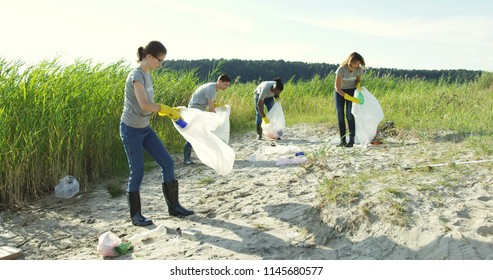 Group of young volunteers helping to keep nature clean and picking up the garbage from a sandy shore.