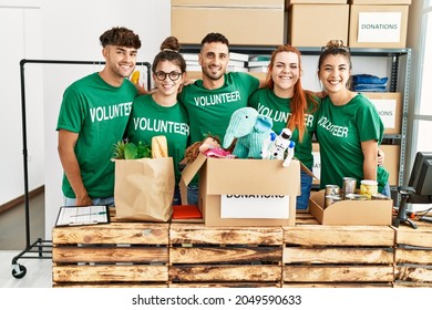 Group of young volunteers smiing happy looking to the camera standing at charity center.