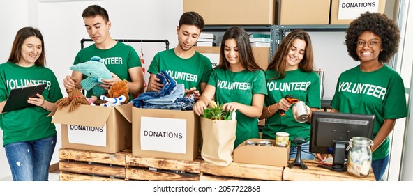 Group of young volunteers smiing happy working at charity center.