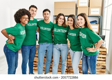 Group of young volunteers smiing happy and hugging standing at charity center.