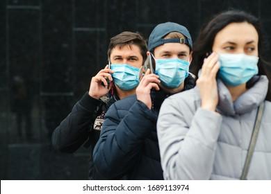 Gruppe junger Freiwilliger, die Gesichtsmasken mit Mobiltelefonen tragen. Freiwillige sind bereit zu helfen. Rufen Sie Freiwillige an. Konzept der gegenseitigen Unterstützung und Unterstützung. Weltweite Koronavirus-Pandemie.