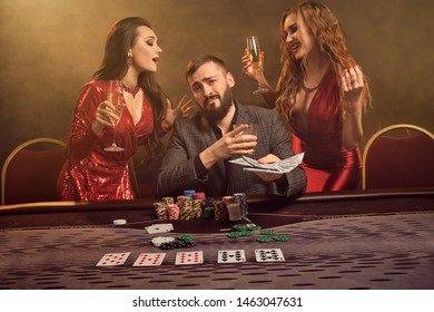 Group of a young wealthy friends are playing poker at a casino.